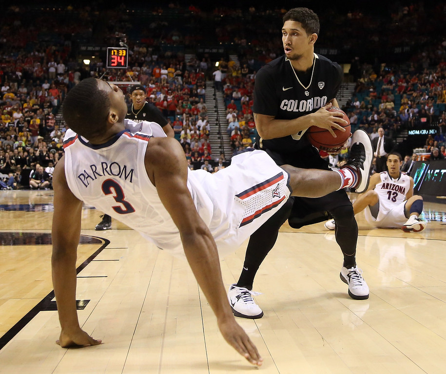 . Askia Booker #0 of the Colorado Buffaloes is called for a charge against Kevin Parrom #3 of the Arizona Wildcats in the first half during the quarterfinals of the Pac-12 tournament at the MGM Grand Garden Arena on March 14, 2013 in Las Vegas, Nevada.  (Photo by Jeff Gross/Getty Images)