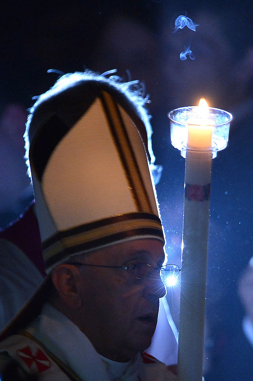 . Pope Francis holds a candle during the Easter Vigil at the St Peter basilica in Vatican. Easter Vigil, also called the Paschal Vigil is a service held in traditional Christian churches as the first official celebration of the Resurrection of Jesus.  AFP PHOTO / FILIPPO MONTEFORTE/AFP/Getty Images