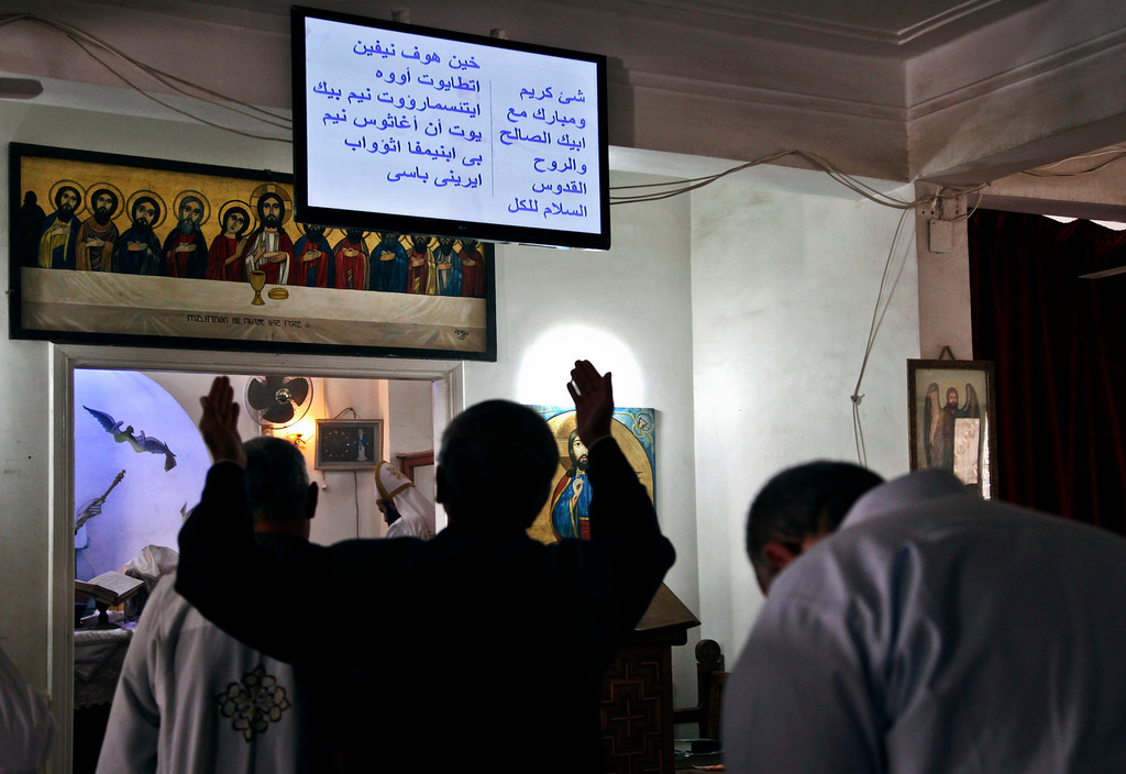 . In this Wednesday, March 27, 2013 photo, Egyptians celebrate mass, reading the Arabic service on a computer screen, in the Coptic Orthodox Church in Samalout, in the province of Minya, Egypt. In Minya where Christians make up about 35 percent of the population,  kidnapping wealthy Christians for ransom is not unheard of, but  30 cases in the last two months alone, has given to soul searching about being a Christian in a country where Muslims are an overwhelming majority and Islamists, including many hardliners, have risen to power.(AP Photo/Thomas Hartwell)