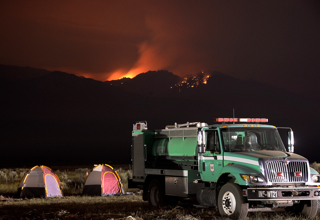 . US Forest firefighters get their rest in tents at the command post as the fire lights up the night skies from the Mountain Fire near Idyllwild, California July 18, 2013. The blaze erupted on Monday afternoon about 100 miles (161 km) east of Los Angeles in the scenic but rugged San Jacinto Mountains that overlook Palm Springs, Rancho Mirage and several smaller desert towns.  Photo by Gene Blevins/LA Dailynews