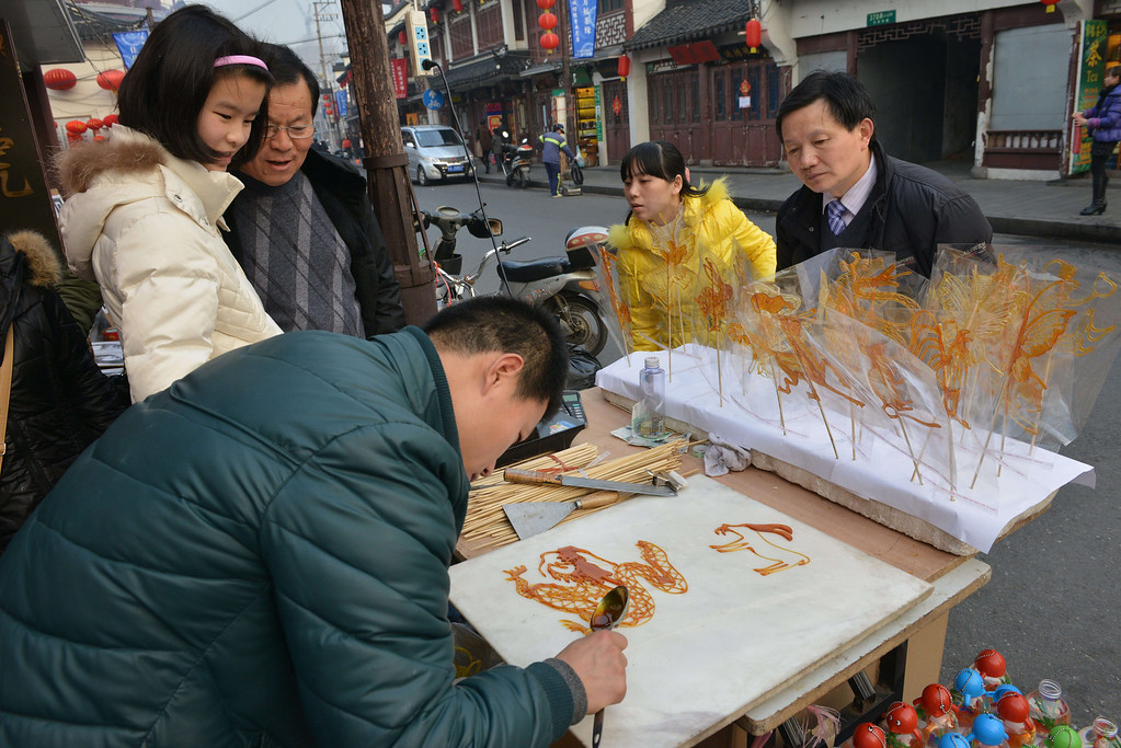 . A man makes Chinese Zodiac animals from candy at a Chinese New Year street fair on the eve of the holiday in Shanghai on January 30, 2014.  AFP PHOTO/Peter PARKS/AFP/Getty Images