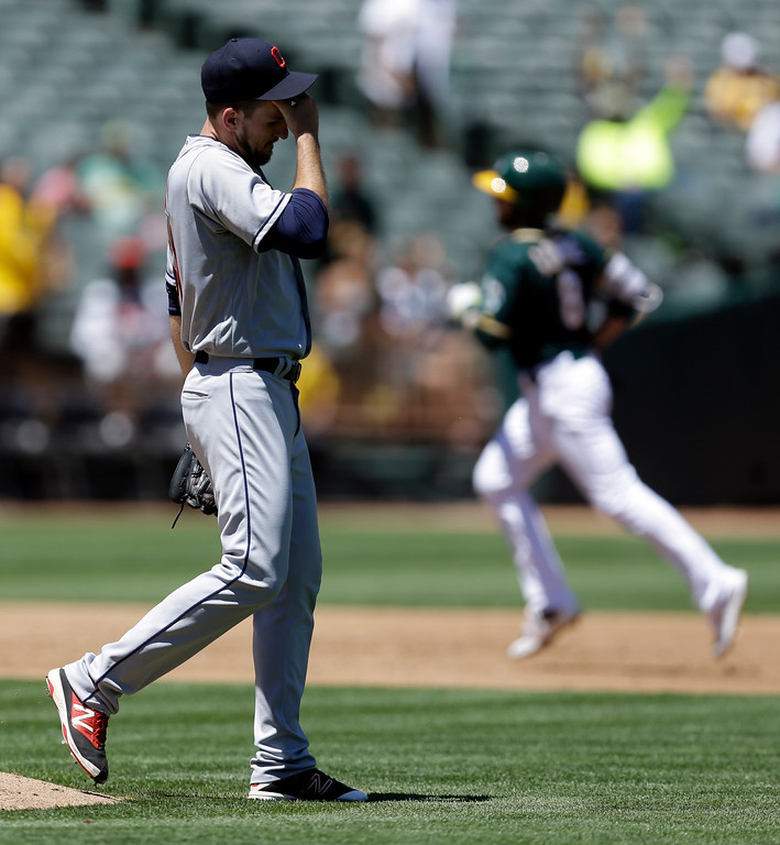 . Cleveland Indians\' Dan Otero, left, places his hand to his head as he waits for Oakland Athletics\' Jed Lowrie, right, to run the bases after Lowrie hit a home run in the third inning of a baseball game Sunday, July 16, 2017, in Oakland, Calif. (AP Photo/Ben Margot)
