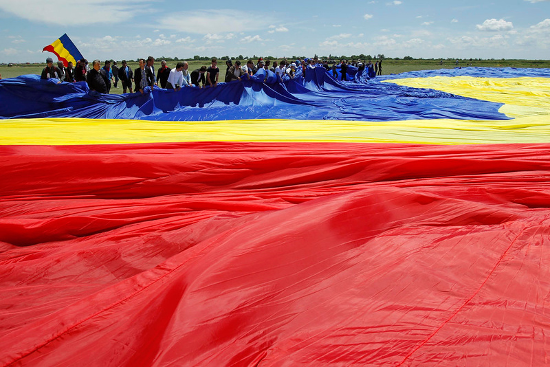 . Workers arrange Romania\'s national flag during a Guinness World Record attempt for the world\'s biggest national flag in Clinceni, near Bucharest May 27, 2013. The flag, measuring 349.4 per 226.9 meters, established a new Guinness World Record. REUTERS/Bogdan Cristel
