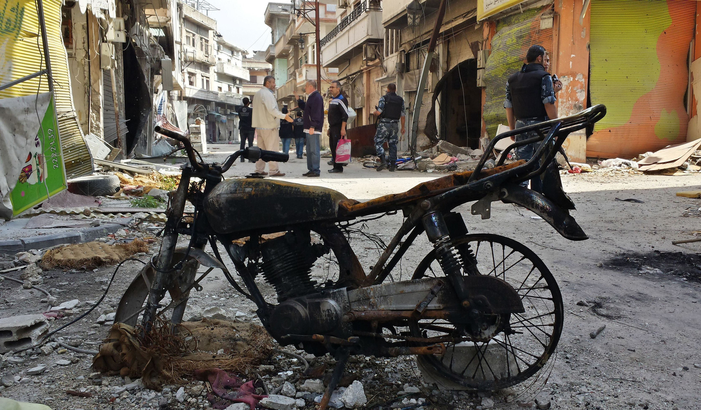 . A burnt out motorcycle is seen in front of people and Syrian government forces walking in a street on May 9, 2014 in the Christian neighborhood of Hamidiyeh in the old city of Homs after Syrian government forces regained control of rebel-controlled areas. The last Syrian rebels left Homs\' Old City under an evacuation deal that hands the government a symbolic victory, as civilians began trickling back in to find neighbourhoods in rubble. (YOUSSEF KARWASHAN/AFP/Getty Images)
