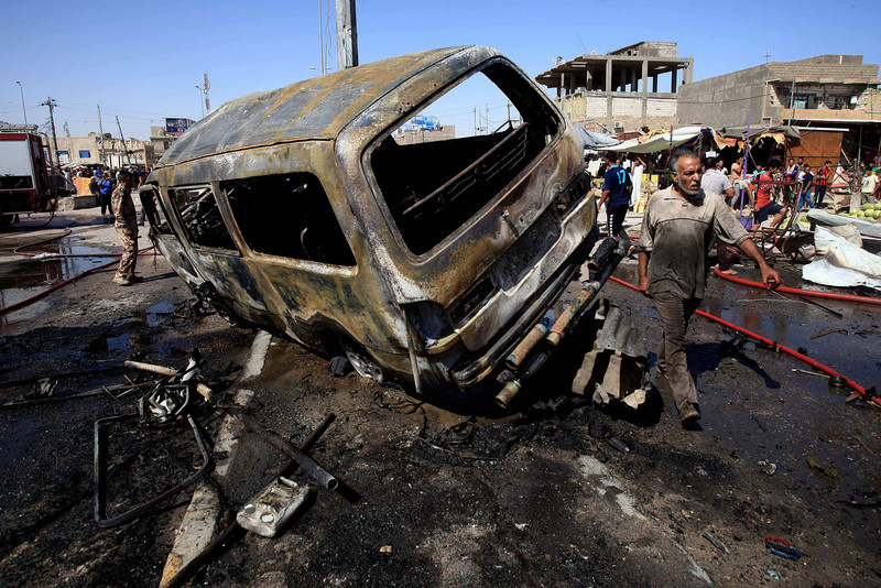 . People and security forces inspect the site of a car bomb explosion in Basra, 340 miles (550 kilometers) southeast of Baghdad, Iraq, Monday, July 29, 2013. A wave of over a dozen car bombings hit central and southern Iraq during morning rush hour on Monday, officials said, killing scores in the latest coordinated attack by insurgents determined to undermine the government. (AP Photo/Nabil al-Jurani)