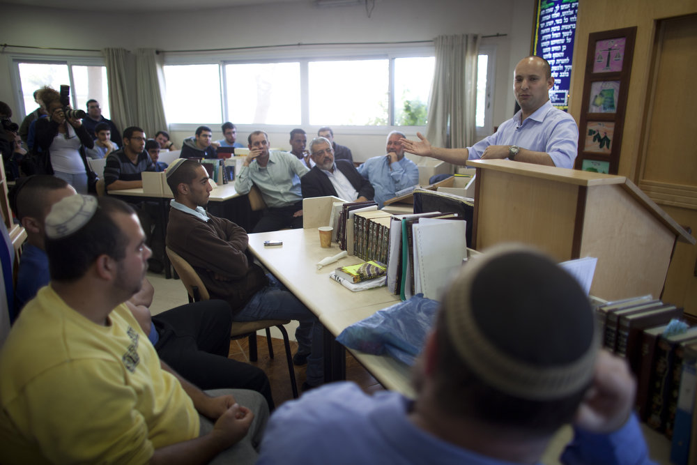 Description of . Naftali Bennett, head of HaBayit HaYehudi Party, the Jewish Home party, campaigns at a pre-army training school at the Shapira Center on January 20, 2013 near Ashkelon, Israel. The religious Jewish Home party is challenging Benjamin Netanyahu's Likud party as Israel heads for a general election on January 22.  (Photo by Uriel Sinai/Getty Images)