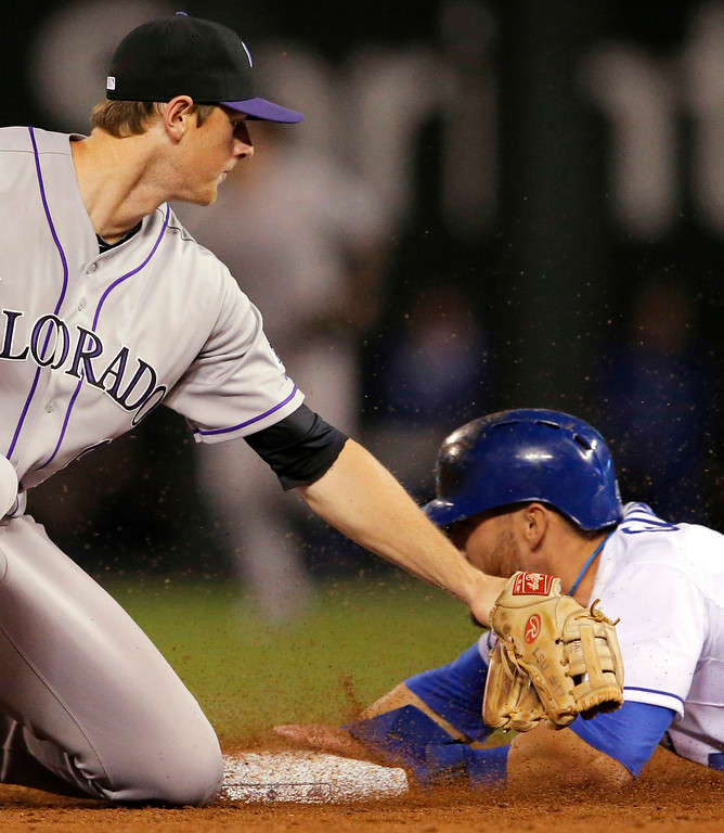 . Kansas City Royals\' Alex Gordon, right, beats the tag by Colorado Rockies second baseman DJ Lemahieu, left, during the fifth inning of a baseball game at Kauffman Stadium in Kansas City, Mo., Tuesday, May 13, 2014. Gordon was safe with a stolen base on the play. (AP Photo/Orlin Wagner)