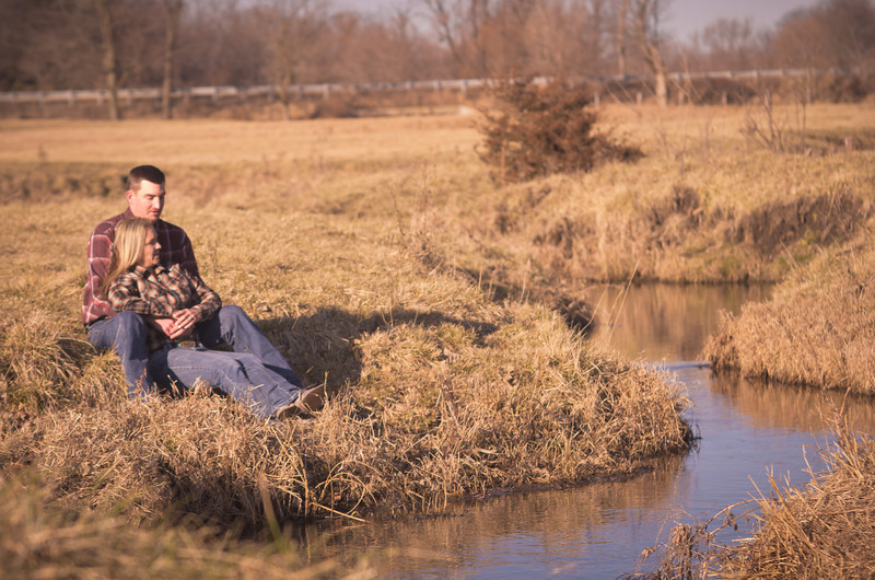 Couple sit together near a creek at a family ranch during winter outdoor engagement photos near Severson Dells in Rockford, IL