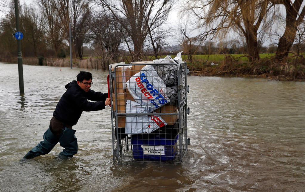 . A local resident pushes belongings on a cart through the flooded part of the town of Staines-upon-Thames, England, as a police van patrols the area, Wednesday, Feb. 12, 2014. (AP Photo/Lefteris Pitarakis)