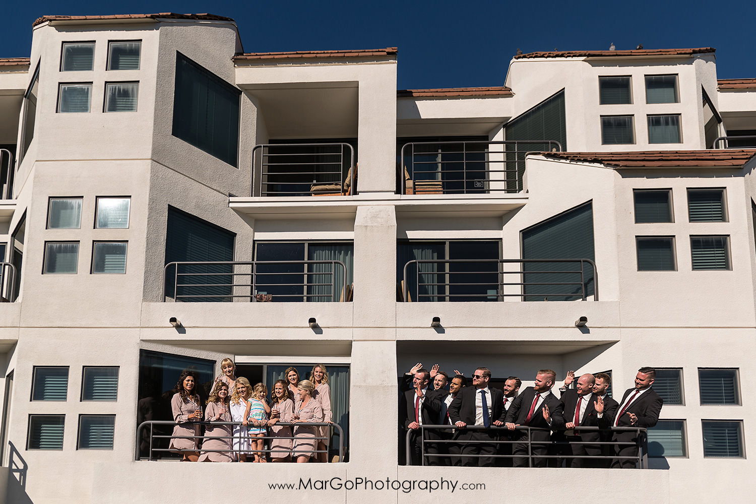 bride and bridesmaids in robes and groom and groomsmen on the balcony in San Diego Hyatt Regency Mission Bay Hotel
