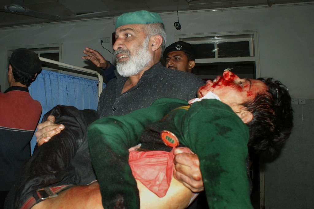 . A Pakistani man carries an injured student at a hospital following an attack by Taliban gunmen on a school in Peshawar on December 16, 2014. Taliban insurgents killed at least 130 people, most of them children, after storming an army-run school in Pakistan December 16 in one of the country\'s bloodiest attacks in recent years. AFP PHOTO/ A MAJEEDA Majeed/AFP/Getty Images