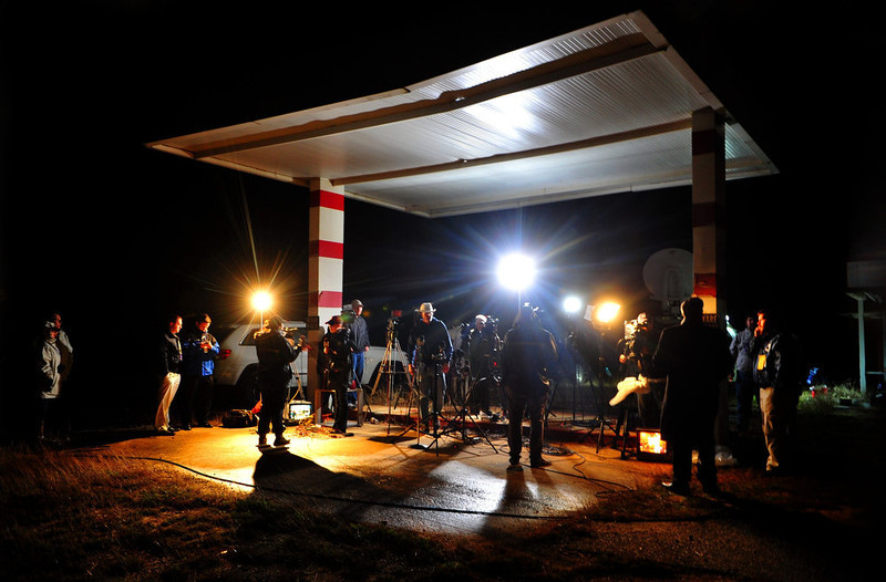 . In this Wednesday, Jan 30, 2013 photo, media outlets those from around the state of Alabama broadcast while covering the ongoing hostage crisis, in Midland City Ala. Police, SWAT teams and negotiators were at a rural property where a man was believed to be holed up in a homemade bunker Wednesday  after fatally shooting the driver of a school bus and fleeing with a 6-year-old child passenger, authorities said. (AP Photo/Dothan Eagle, Jay Hare)