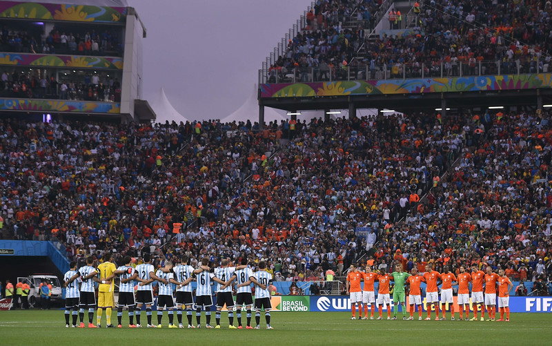 . Argentina\'s (L) and the Netherlands\' teams line up prior to the semi-final football match between Netherlands and Argentina of the FIFA World Cup at The Corinthians Arena in Sao Paulo on July 9, 2014. (FABRICE COFFRINI/AFP/Getty Images)