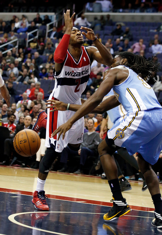 . Washington Wizards guard John Wall (2) has the ball stripped by Denver Nuggets forward Kenneth Faried (35) in the first half of an NBA basketball game on Monday, Dec. 9, 2013, in Washington. The Nuggets won 75-74. (AP Photo/Alex Brandon)