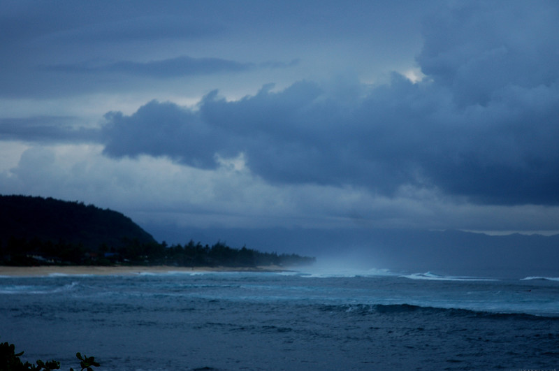 Dreamy deep blue storm clouds fill the sky, scattering rain as they move over the dark blue ocean at sunset   Sunset Beach on the North Shore of O'ahu, Hawai'i
