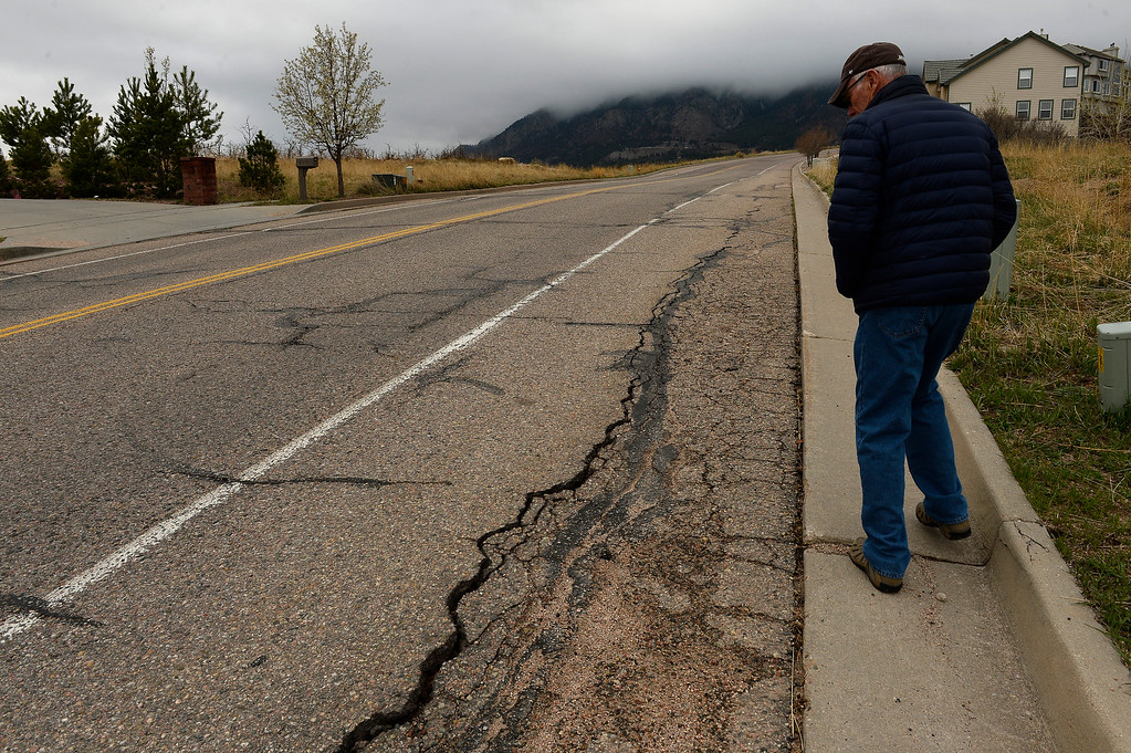 . Homeowner Denny Cripps walks along his street where cracks from the ancient landslide are beginning to show up on the main street outside of his home in Broadmoor Bluffs on April 11, 2016 in Colorado Springs, Colorado.  The Cripps are among 200 homeowners who have applied for federal bailouts because their home is being eaten up by collapsing expansive soil that is part of an ancient and massive landslide area.  Their home has cracked walls, uneven floors and is literally sliding down the mountain.  It is a problem that city officials have known about since the mid-1990\'s when city planners approved developments on what geologists have called some of the most unstable geology on the front range.  (Photo by Helen H. Richardson/The Denver Post)