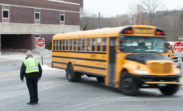 03/21/18 Wesley Bunnell | Staff New Britain High School Resource Officer Jerzy Chmura directs the line of buses leaving the school on early dismissal due to the nor'easter expected later in the day on Wednesday.