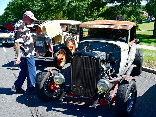 9/21/2019 Mike Orazzi | StaffrBill Ogo of Terryville looks over one the cars on display during Saturday's Mum Festival on Memorial Boulevard in Bristol.