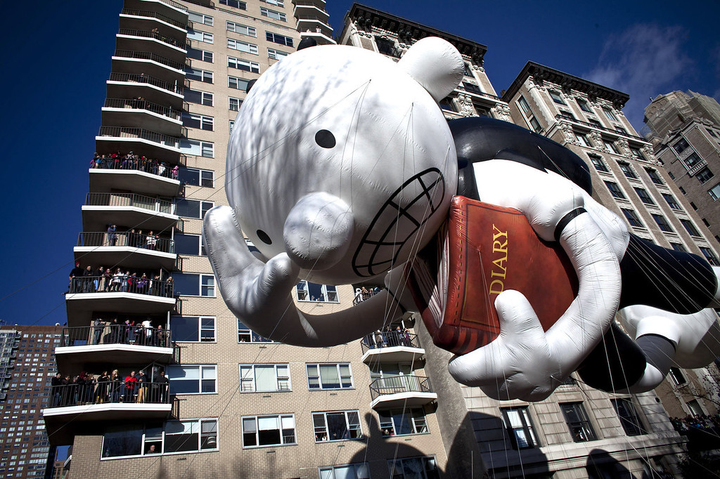 . Residents in an apartment block watch as giant balloons float past during the Macy\'s Thanksgiving Day Parade on November 28, 2013 in New York City. Despite earlier concerns about the wind, the balloons flew as planned for the parade. (Photo by Kena Betancur/Getty Images)