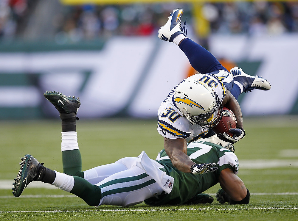 . Running back Ronnie Brown #30 of the San Diego Chargers us upended by Yeremiah Bell #37 of the New York Jets during the first half in a game at MetLife Stadium on December 23, 2012 in East Rutherford, New Jersey. (Photo by Rich Schultz /Getty Images)