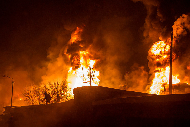 . In this photo provided by the Ministry of Emergency Situations Kirov Branch press service, men are silhouetted against burning tankers early Wednesday, Feb. 5, 2014, near Posdino in Kirov region of Russia, some 800 km ( about 500 miles) northeast of Moscow. 32 tankers were derailed and 12 of them burned. No casualties were reported. (AP Photo/ Ministry of Emergency Situations, Kirov Branch Press Service)