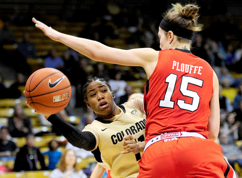 . Colorado\'s Brittany Wilson (left) passes the ball under the reach of Utah\'s Michelle Plouffe (right) during their basketball game at the University of Colorado in Boulder , Colorado January 8, 2013. BOULDER DAILY CAMERA/ Mark Leffingwell