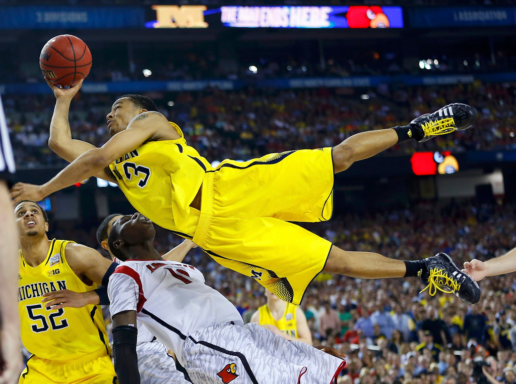 . Michigan Wolverines guard Trey Burke (3) drives to the hoop on Louisville Cardinals center Gorgui Dieng during the second half of their NCAA men\'s Final Four championship basketball game in Atlanta, Georgia April 8, 2013.  REUTERS/Jeff Haynes