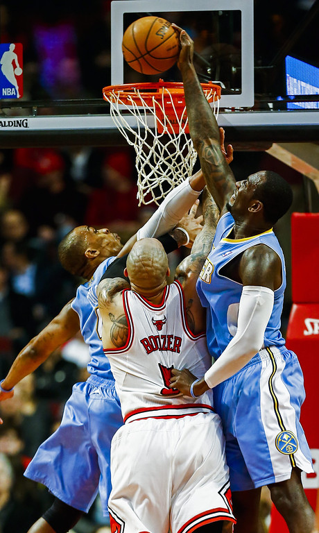 . Denver Nuggets center J.J. Hickson (R) swats the ball away from the basket and over Chicago Bulls forward Carlos Boozer (C) and Denver Nuggets guard Randy Foye (L) in the first half of their NBA game at the United Center in Chicago, Illinois, USA, 21 February 2014  EPA/TANNEN MAURY