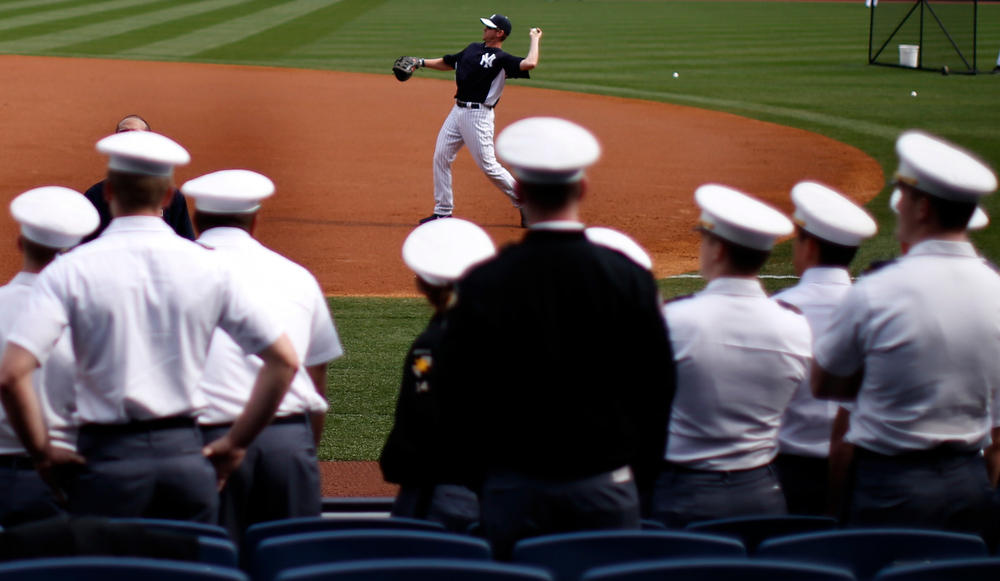 . Cadets from the U.S. military academy at West Point watch from the stands as New York Yankees players warm up during batting practice at Yankee Stadium before the Yankees\' opening day MLB American League baseball game against the Boston Red Sox in New York, April 1, 2013.  REUTERS/Mike Segar