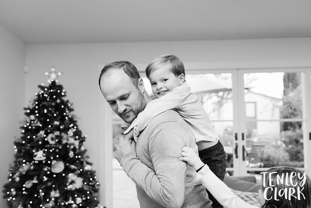 Boy on father's back in front of Christmas tree. Lifestyle in-home family photoshoot in Marin, CA by Tenley Clark Photography.
