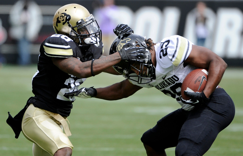 . BOULDER, CO.- APRIL13: John Walker, left, holds on tight to Josh Ford. The University of Colorado football team hosts its spring football game at Folsom Field under the direction of new head coach Mike MacIntyre. (Photo By Kathryn Scott Osler/The Denver Post)