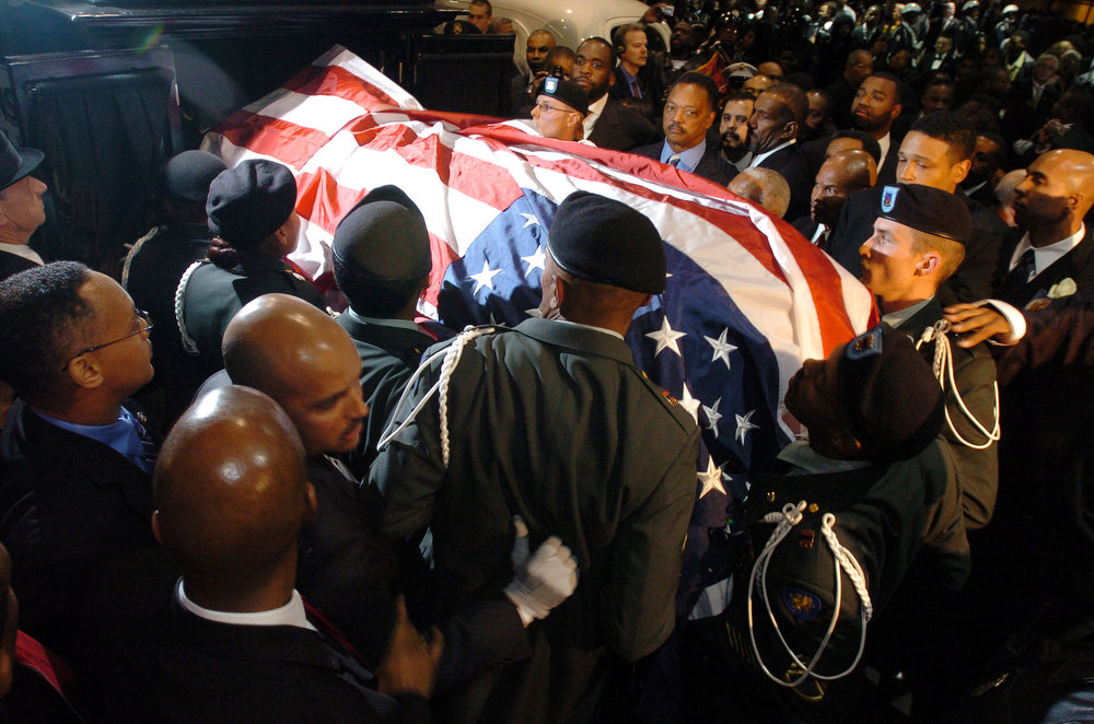 Description of . A military honor guard carries the casket containing civil rights pioneer Rosa Parks out of Greater Grace Temple as Jesse Jackson (top center) and Detroit Mayor Kwame Kilpatrick, next to Jackson, look on after her funeral service on November 2, 2005 in Detroit, Michigan. The funeral lasted more the seven hours with more then 20 speakers. In 1955, Rosa Parks was arrested in Montgomery, Alabama for refusing to give up her seat on a bus to a white man, an incident which sparked the civil rights movement.February 4, 2013 will mark 100 years since the birth of civil rights activist Rosa Parks who was brought to attention when in 1955 she refused to give up her seat on a bus for a white passenger in Alabama.  (Photo by Bryan Mitchell/Getty Images)