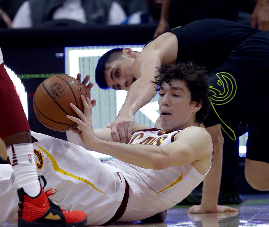 . Cleveland Cavaliers forward Cedi Osman, front, comes up with a loose ball against Atlanta Hawks forward Ersan Ilyasova during the first half of an NBA basketball game Friday, Feb. 9, 2018, in Atlanta. Cleveland won 123-107. (AP Photo/John Bazemore)