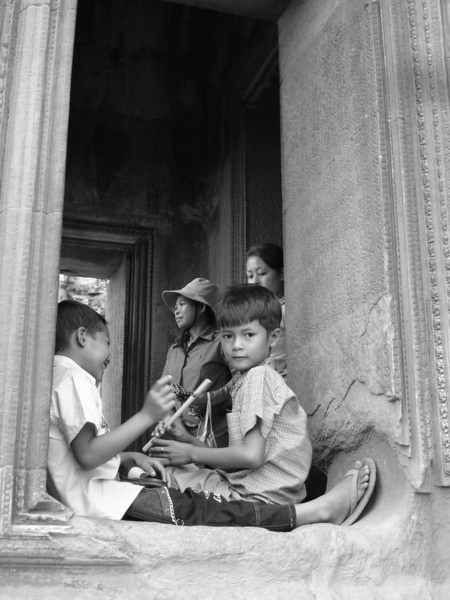 kids selling flutes in a tower in Angkor Wat