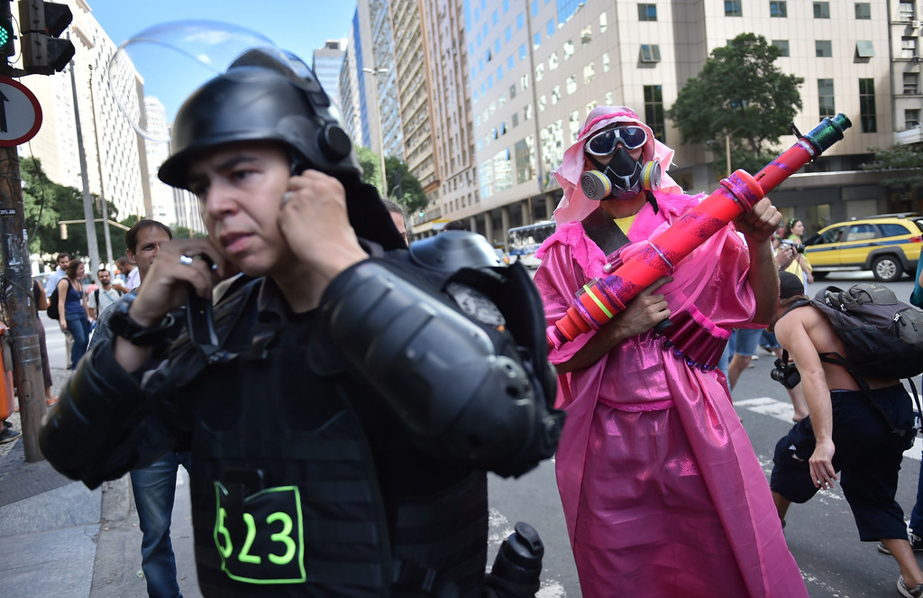 . A demonstrator (R) wearing a gas mask stands next to a riot policeman during an anti-World Cup protest in Rio de Janeiro on June 12, 2014. Brazil was nervously gearing up for the start of the World Cup on Thursday with the host nation preparing to launch the month-long carnival as scattered protests broke out just hours from kick-off.   AFP PHOTO / YASUYOSHI CHIBA/AFP/Getty Images
