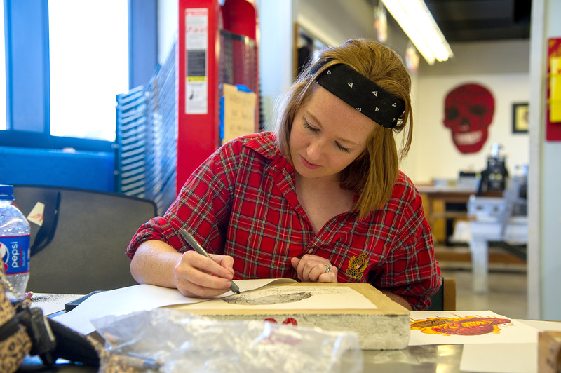 Student Ashley McGee details her lithograph print for Advanced Printmaking.