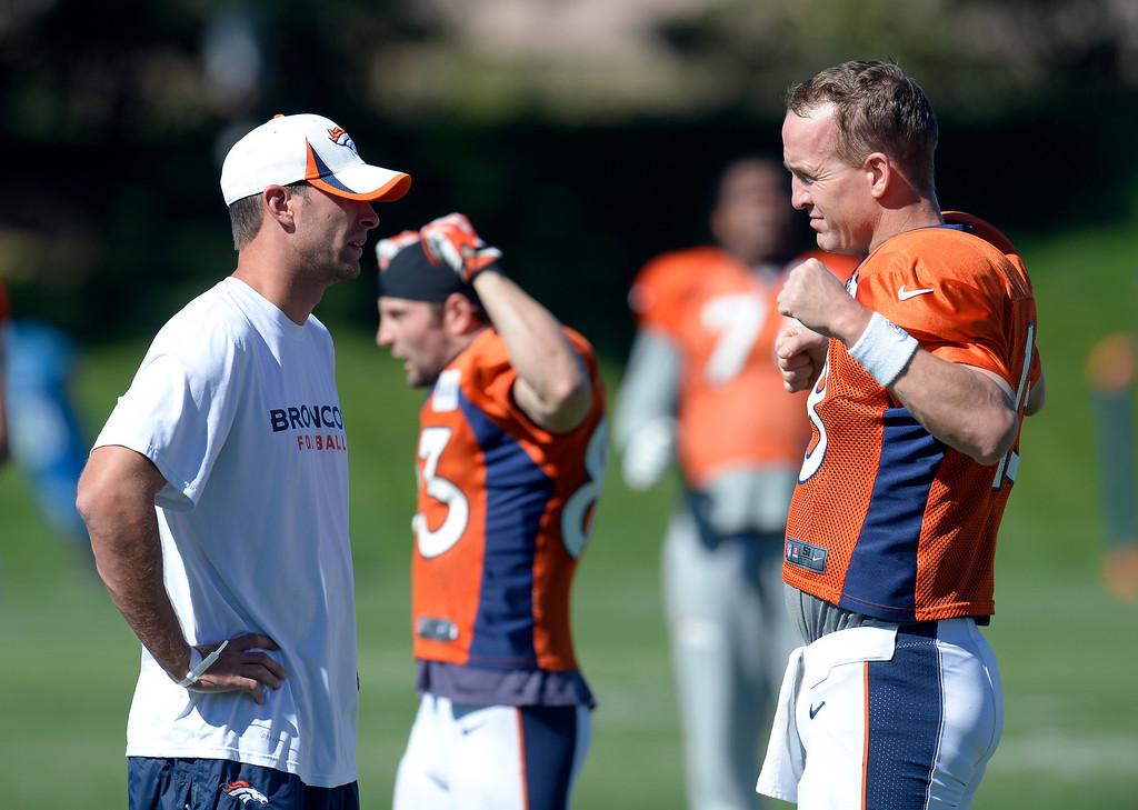 . Denver Broncos offensive coordinator Adam Gase talks with Denver Broncos quarterback Peyton Manning (18) before practice October 2, 2013 at Dove Valley. (Photo by John Leyba/The Denver Post)