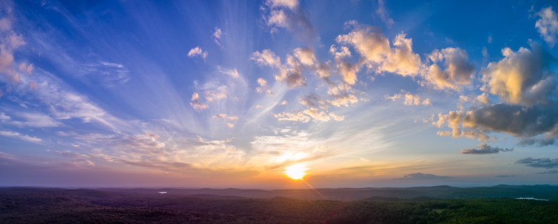 Panoramic sunset with light, puffy clouds in the sky overlooking summer New England forests. High resolution HDR panorama from drone