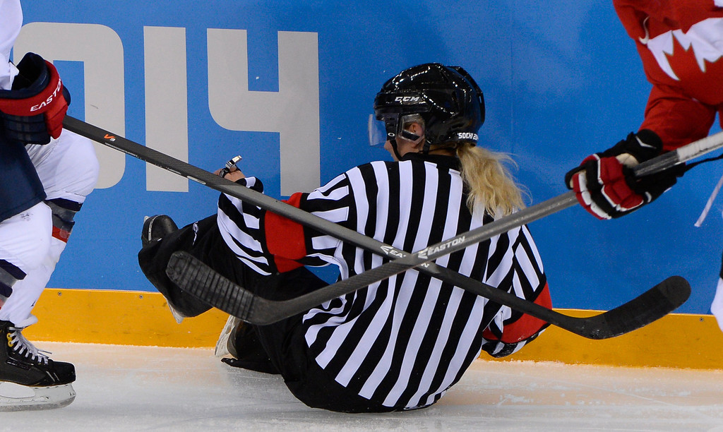 . A referee falls on the ice in between two players during the Women\'s Ice Hockey Group A match between Canada and USA at the Sochi Winter Olympics on February 12, 2014 at the Shayba Arena. AFP PHOTO / JONATHAN NACKSTRAND/AFP/Getty Images