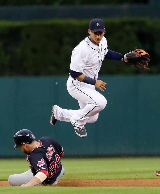 . Detroit Tigers shortstop Jose Iglesias avoids Cleveland Indians\' Jason Kipnis after turning the ball to get a double play on Carlos Santana at first base during the third inning of a baseball game Friday, June 12, 2015, in Detroit. (AP Photo/Duane Burleson)