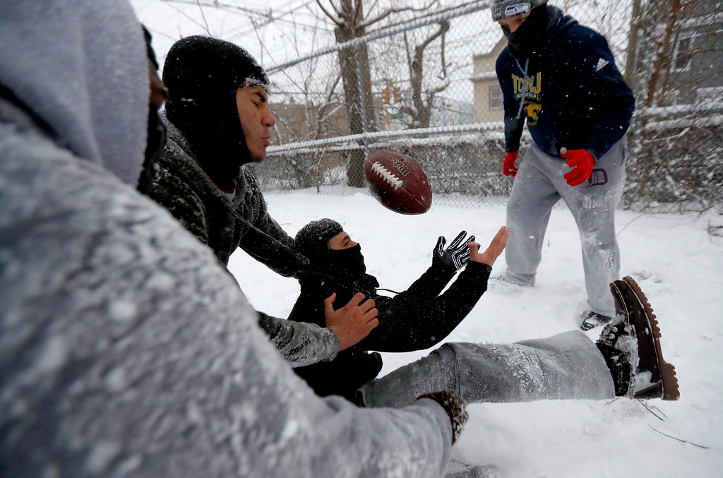 . A teen fumbles the ball while playing a game of pick-up football under a snow storm at Leonard Gordon Park, Saturday, Jan. 7, 2017, in Jersey City, N.J. (AP Photo/Julio Cortez)