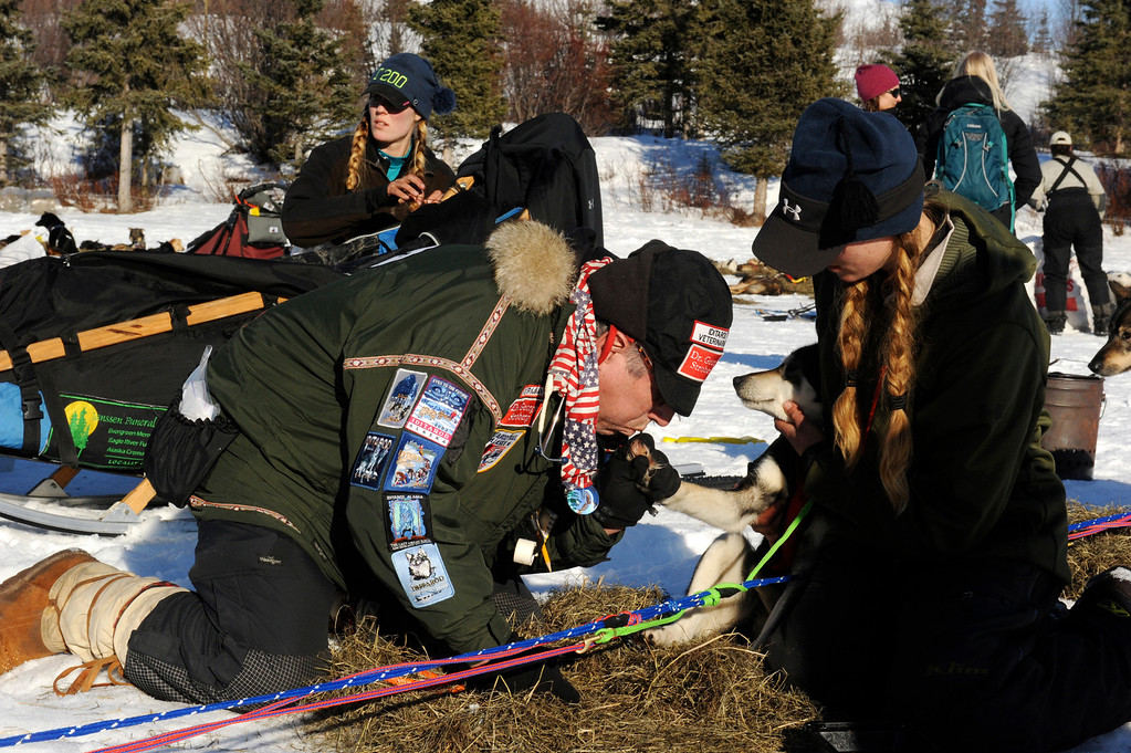 . In this March 3, 2014 photo, Iditarod veterinarian George Stroberg, left, blows on Precious\'s paw as Anna Berington holds her at the Rainy Pass checkpoint during the 2014 Iditarod Trail Sled Dog Race near Puntilla Lake, Alaska. Precious tore part of a toenail off and the vet snipped off the rest of it and then cauterized it to stop the bleeding. (AP Photo/The Anchorage Daily News, Bob Hallinen)