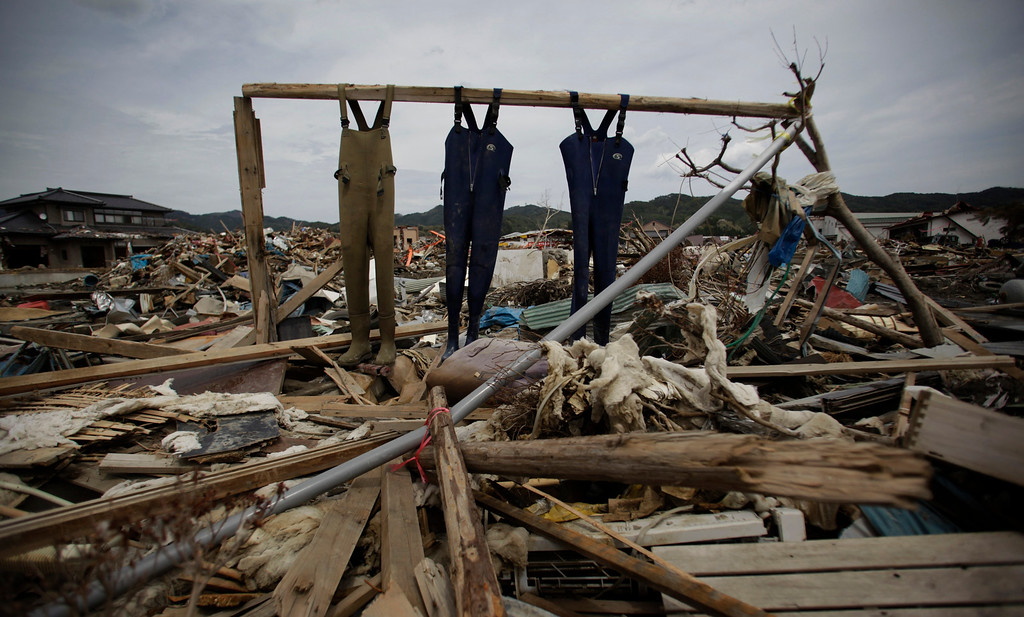 . FILE - In this Tuesday, May 10, 2011, file photo, Fishermen\'s overalls are hung in an area destroyed by the March 11 earthquake and tsunami in Kesennuma, northeastern Japan. (AP Photo/Junji Kurokawa, File)