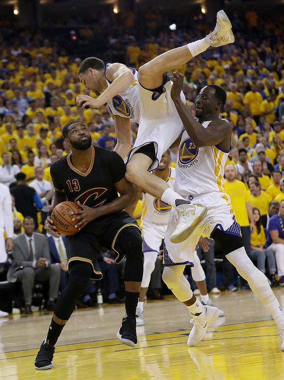 . Cleveland Cavaliers center Tristan Thompson (13) shoots again Golden State Warriors guard Klay Thompson, top, and forward Draymond Green during the second half of Game 5 of basketball\'s NBA Finals in Oakland, Calif., Monday, June 12, 2017. (AP Photo/Marcio Jose Sanchez)