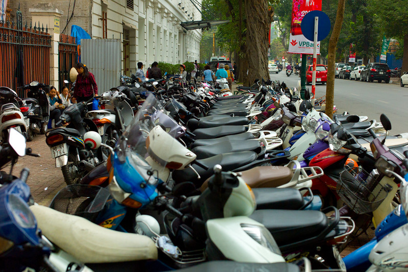 A motorbike parking lot on the sidewalk near the rear (new) entrance to the Sofitel Metropole (white building with canope on the left).  Motorbikes are guarded by entrepreneurs who, for a small fee, watch the bikes to prevent stealing.