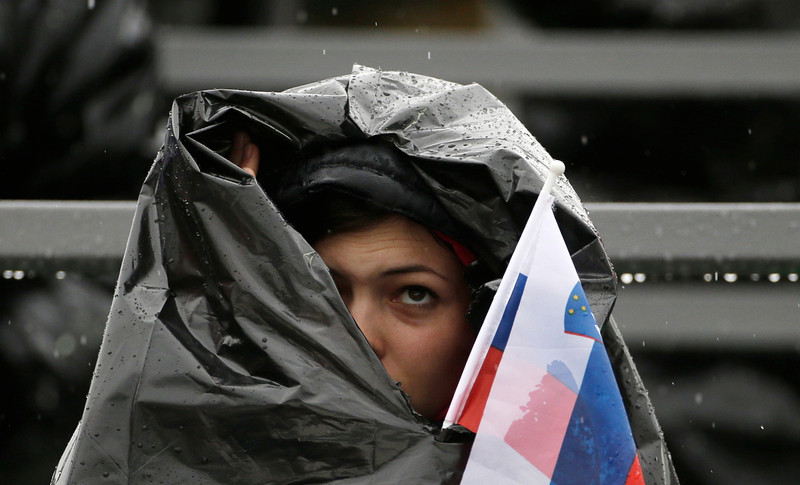. A Russia supporter looks up to the sky as she shields herself against the pouring rain during the Nordic combined individual Gundersen large hill competition at the 2014 Winter Olympics, Tuesday, Feb. 18, 2014, in Krasnaya Polyana, Russia. (AP Photo/Gregorio Borgia)