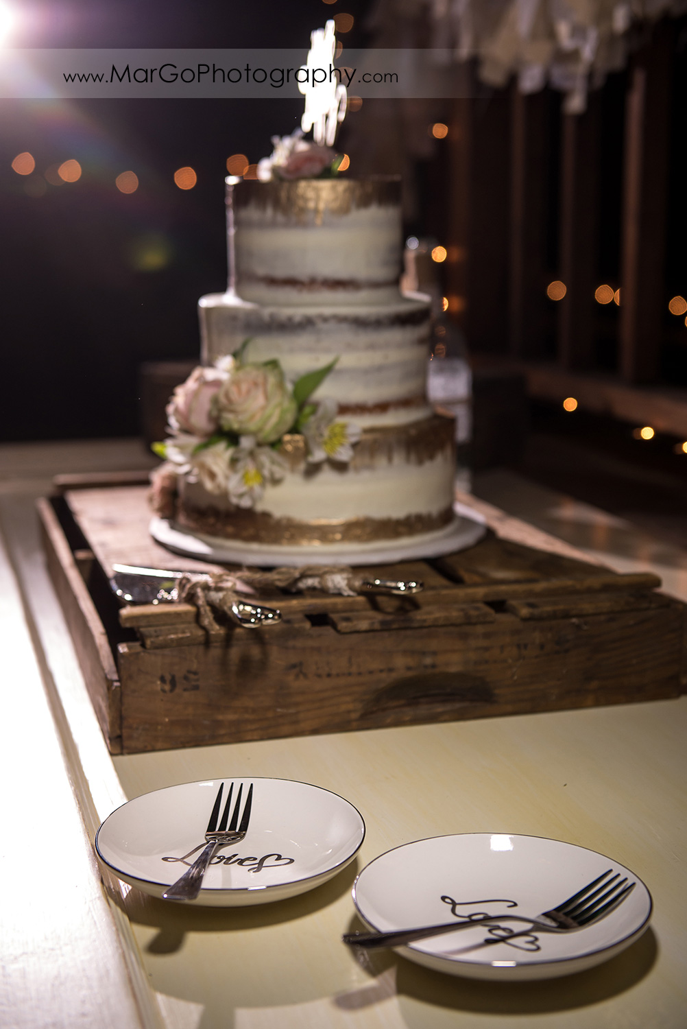 love plates with wedding cake in background at Taber Ranch Vineyards