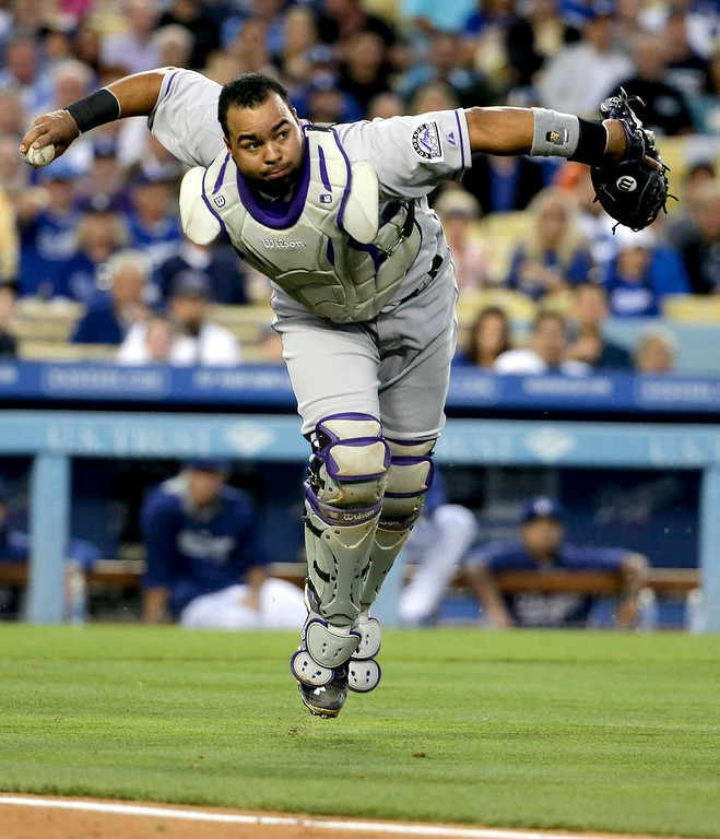 . Colorado Rockies catcher Wilin Rosario throws out Los Angeles Dodgers\' Dee Gordon at first during third inning of a baseball game in Los Angeles, Wednesday, June 18, 2014. (AP Photo/Chris Carlson)