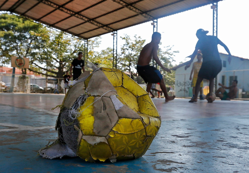 . In this June 8, 2014 photo, a ragged, deflated ball sits at the edge of a collapsing old hangar where boys play street soccer in Itu, on the outskirts of Sao Paulo, Brazil. The boys playing their hearts out here are nervous about Brazil\'s chances of winning the World Cup. Brazil, currently third in the FIFA rankings, is still considered the world\'s greatest soccer nation. (AP Photo/Shuji Kajiyama)