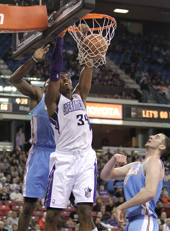 . Sacramento Kings forward Jason Thompson, center, dunks between Denver Nuggets Kenneth Faried, left, and Kosta Koufos during the third quarter of an NBA basketball game in Sacramento, Calif., Sunday, Dec. 16, 2012.  The Nuggets won 122-97.(AP Photo/Rich Pedroncelli)